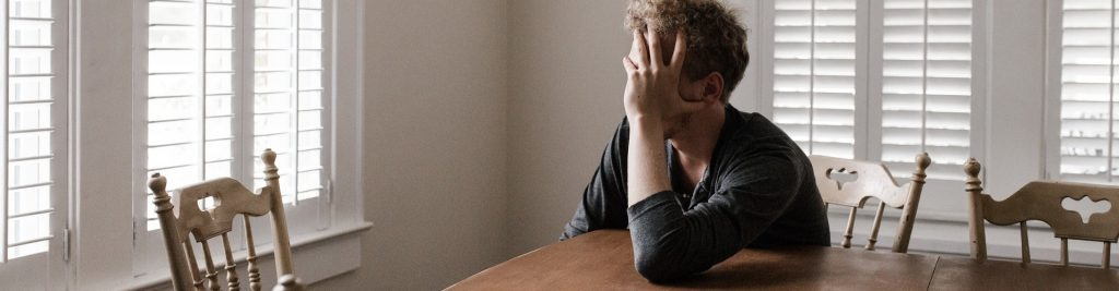 Depressed person at kitchen sitting at kitchen table